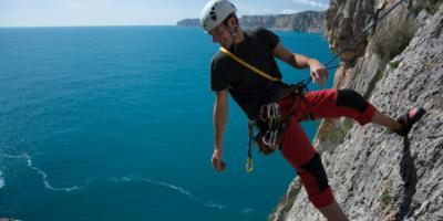 Sport climbing on rock walls by the sea